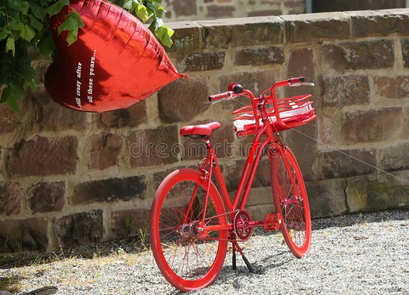 Retro bici rossa davanti ad una parete del castello con un impulso rosso nel fondo immagini stock libere da diritti