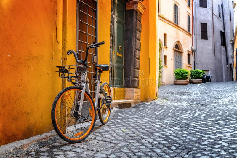Retro bike parked in Rome. Grey and orange bike parked in an ancient and beautiful street of Rome, the Italian capital royalty free stock photos