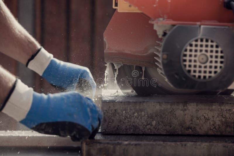 Retro bild av arbetaren som använder en vinkelmolar eller cirkelsåg till royaltyfri bild