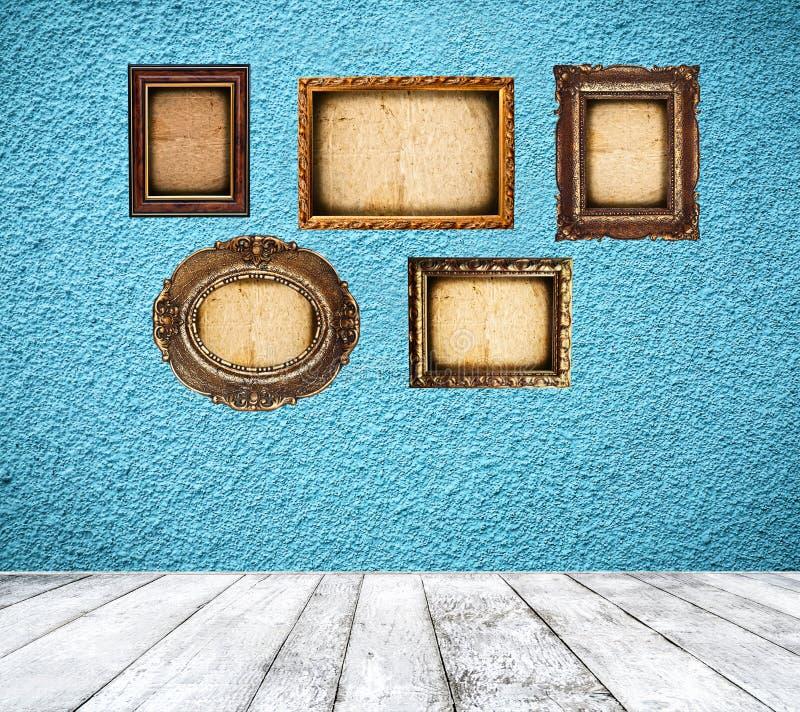 Retro blått rum med tomma ramar royaltyfri bild