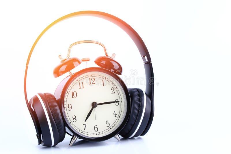 Retro black alarm clock with headphone isolated on white backgr. Ound stock image