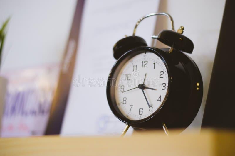 Black retro clock on a shelf in office. Retro black clock on a shelf in sunny office stock photos
