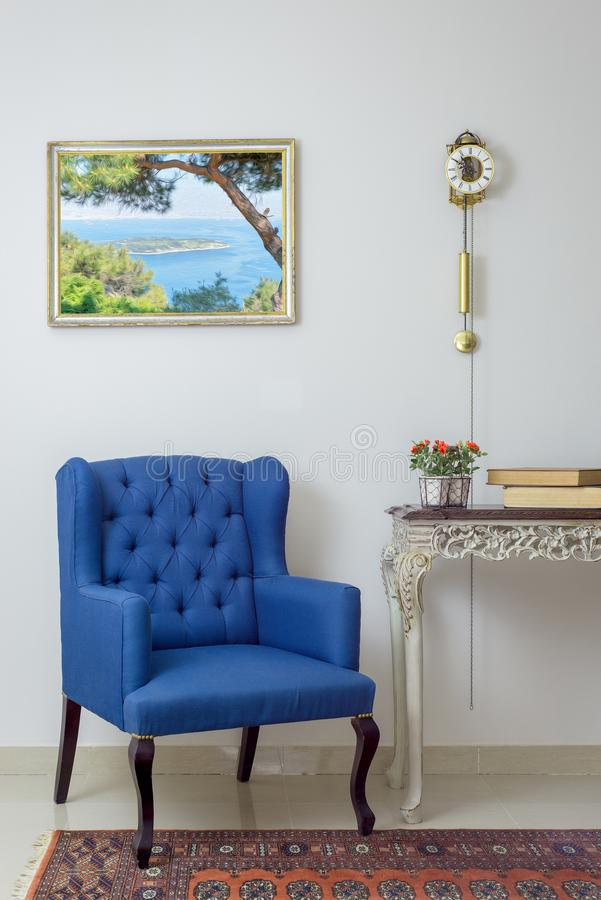 Retro blue armchair, vintage wooden beige table & pendulum clock over off white wall, tiled beige floor and orange ornate carpet stock photo