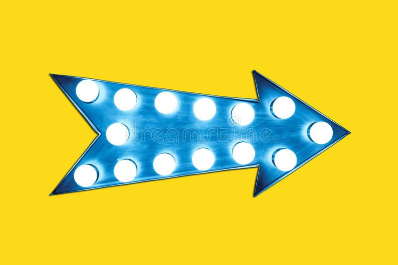 Retro blue arrow shaped vintage colorful illuminated metallic display sign with glowing light bulbs. On a empty vivid yellow background royalty free stock image