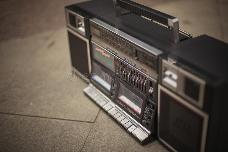 The retro boombox, an outdated portable radio with a cassette recorder from the 80s, stands on the sidewalk. Rap, hip royalty free stock photos