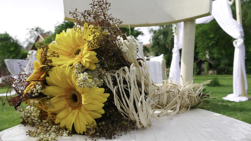 Retro bouquet of yellow  Gerber daisy on a white chair at the wedding stock photography