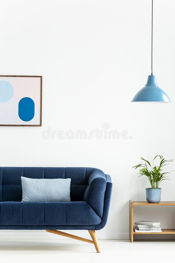 Retro bowl pendant light and a baby blue cushion on a dark, elegant sofa in a simple living room interior with white walls. Real p stock images