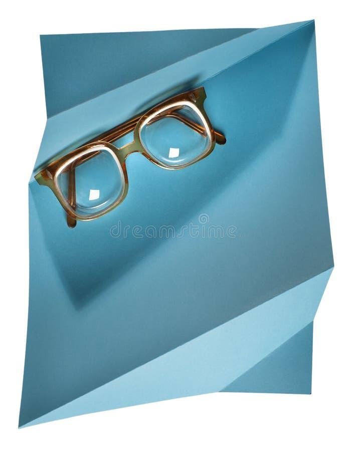 Retro- Brillen des hohen Diopter mit gelbem Rahmen auf blauer kreativer Unterstützung lizenzfreies stockbild