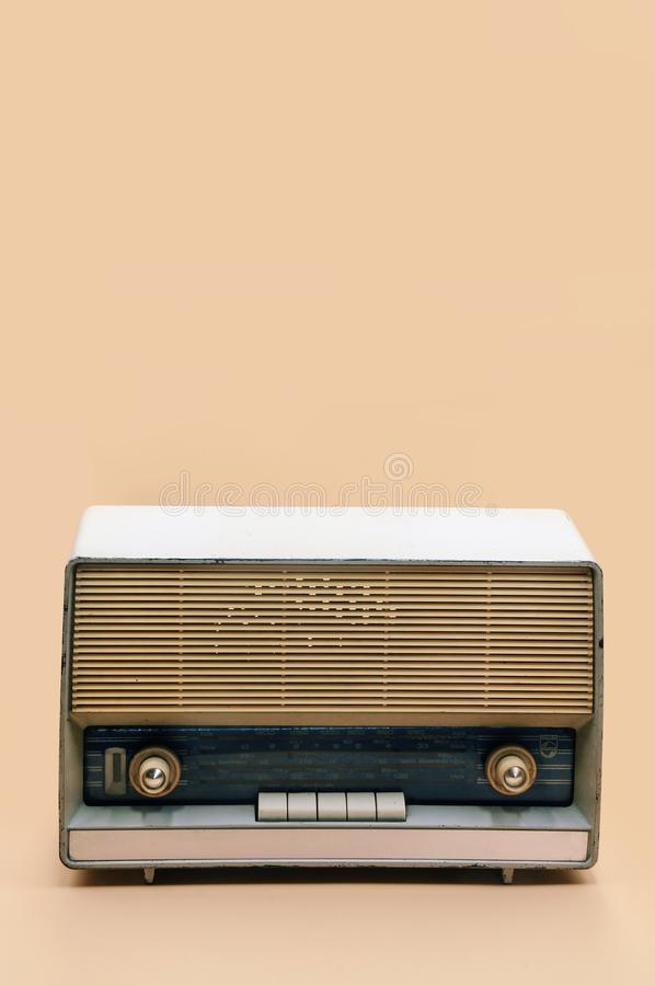 Retro broadcast radio receiver on peach color background. With place for text stock images
