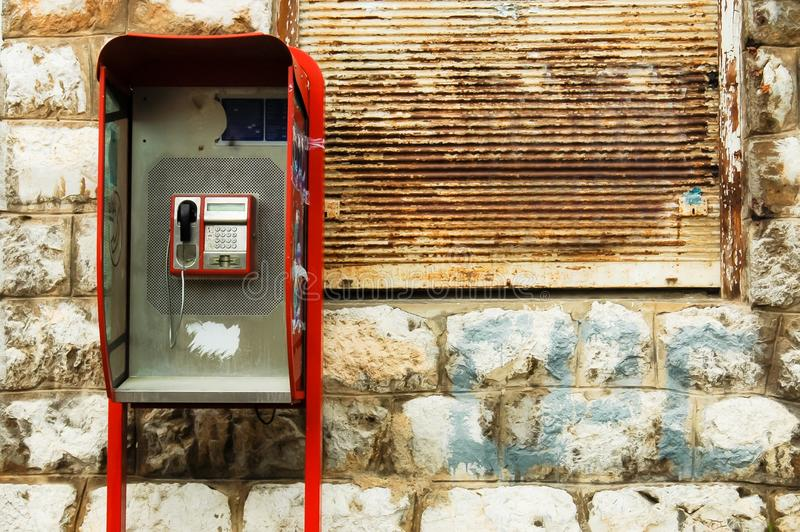 Retro broken red phone booth box. In front of rusty background and stone wall royalty free stock photography