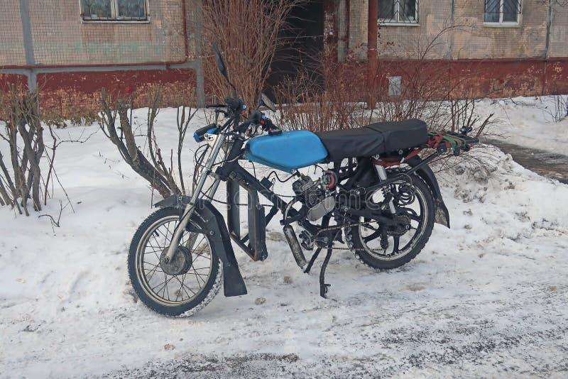 Retro bromfiets in de sneeuw aan de kant van de weg wordt geparkeerd die royalty-vrije stock afbeeldingen