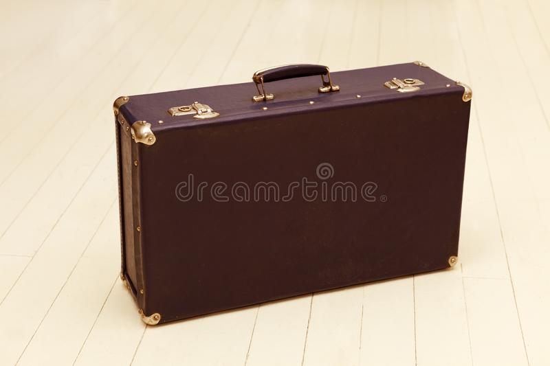 Retro brown suitcase with metal corners on white floor.  royalty free stock image