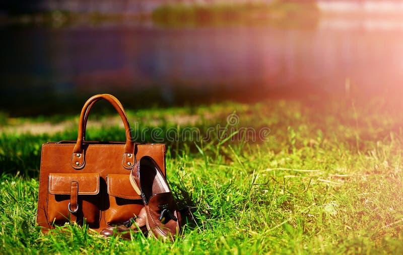 Retro bruine schoenen en zak van het mensenleer in helder kleurrijk de zomergras stock fotografie
