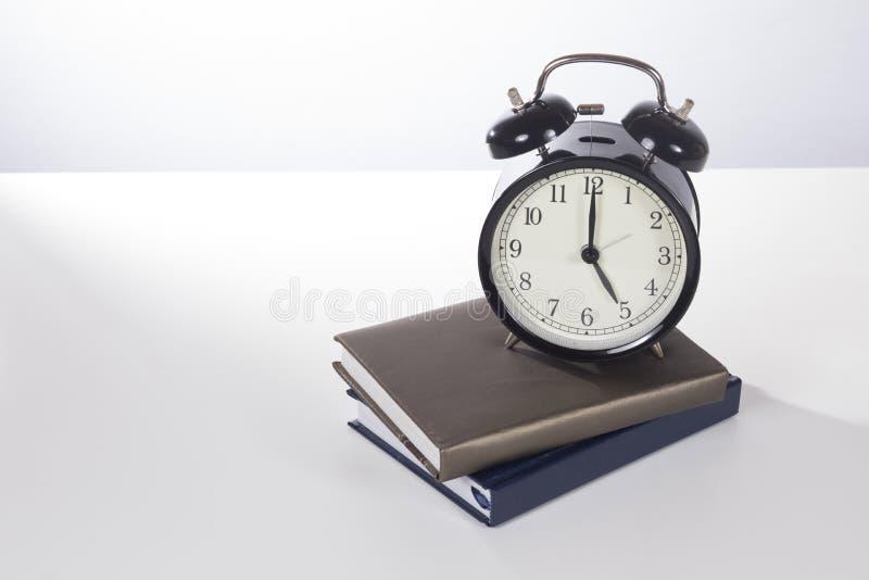 Retro budzik na stosie książki obrazy stock
