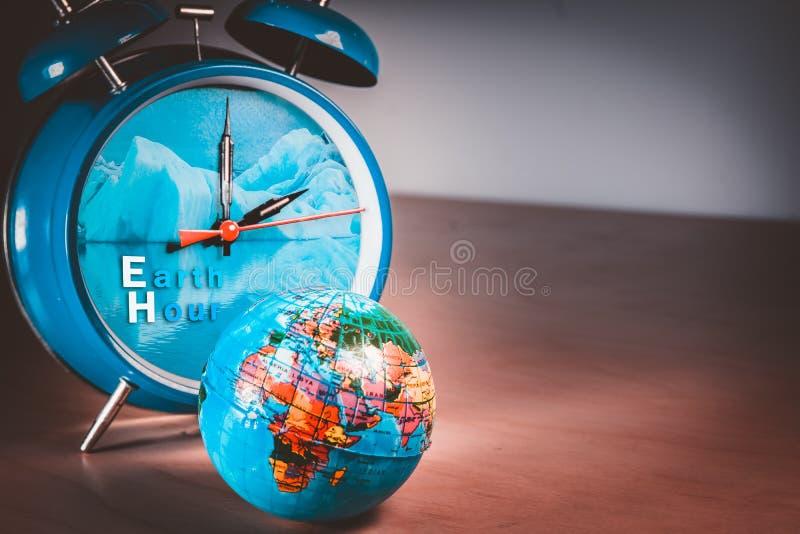 Retro budzik z naturalnym lodowa wizerunkiem i małej światowej kuli ziemskiej balową symbolizuje Ziemską godziną zdjęcia royalty free