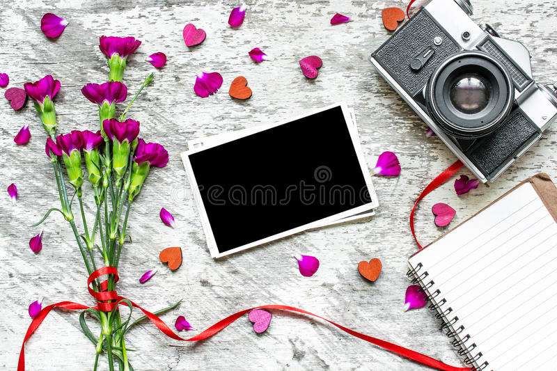 Retro camera and blank photo frame with purple carnation flowers. Petals and lined notebook on rustic wooden background. valentines day background. top view royalty free stock images