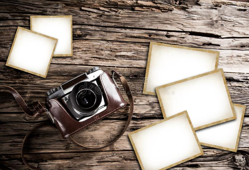 Retro camera and blank photo frames on wooden table. Top view. stock photography