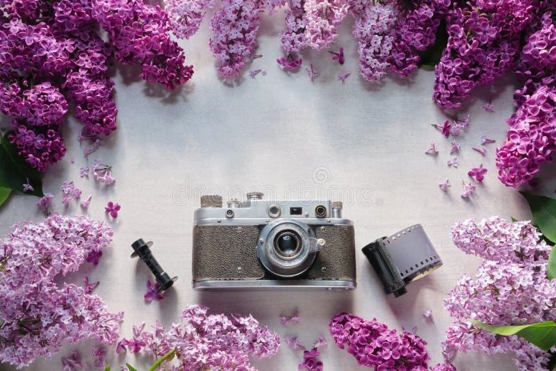 Retro camera, de broodjes van de fotofilm en grens van lilac bloemen Hoogste mening stock fotografie