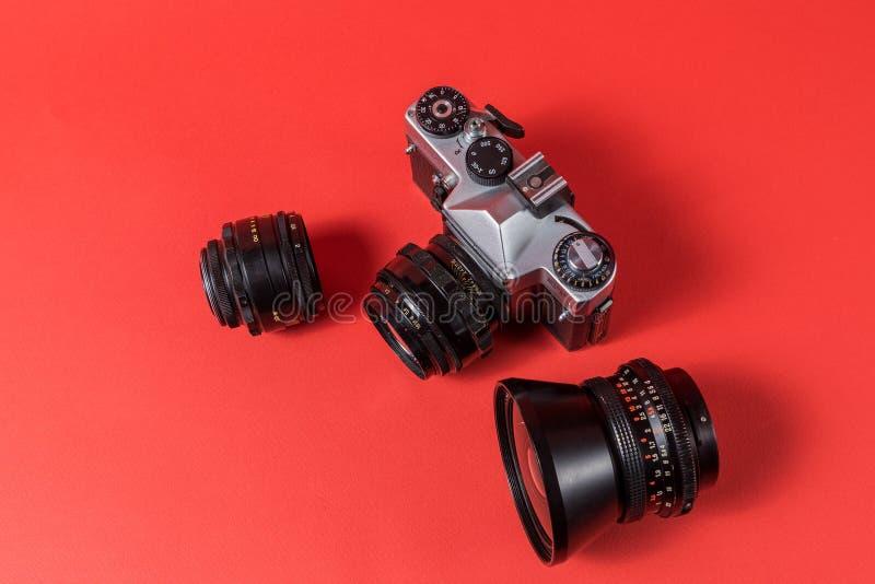 Retro camera en de lenzen van de filmfoto op rode achtergrond wordt geïsoleerd die royalty-vrije stock fotografie