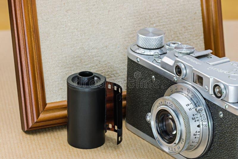 Retro camera, filmbroodje en leeg houten fotokader in wijnoogst royalty-vrije stock afbeelding