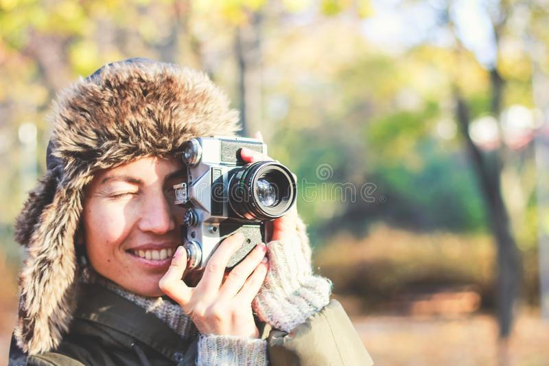 Retro camera in hand of young photographer girl and ready to take photo. stock photography