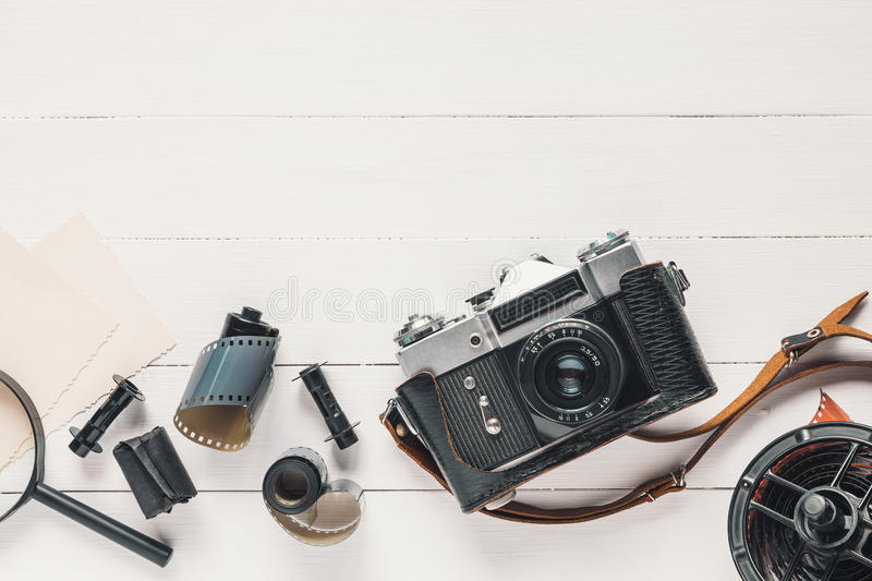 Retro camera, old photo film rolls, empty photos and magnifier royalty free stock images