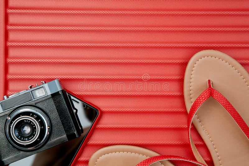 Retro camera and smartphone beside flip-flops on red background. Adventure time conception.  royalty free stock photos