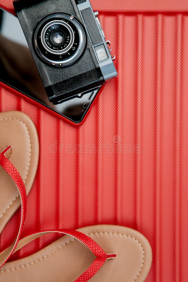 Retro camera and smartphone beside flip-flops on red background. Travel blogging or woman blogger or summer vacation conception.  stock image