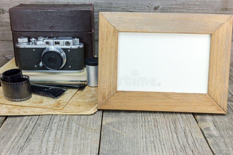 Retro camera, verbiedt films, oude foto's en leeg kader op grijs stock foto's
