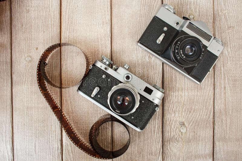 Retro cameras top view. Two retro cameras and a photographic film on a vintage wooden background stock photos