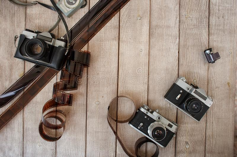Retro cameras top view. Two retro cameras and a photographic film on a vintage wooden background stock image