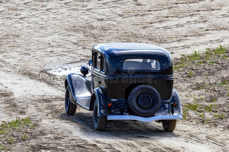 Retro car black rides on the sand.  Top view from behind stock image