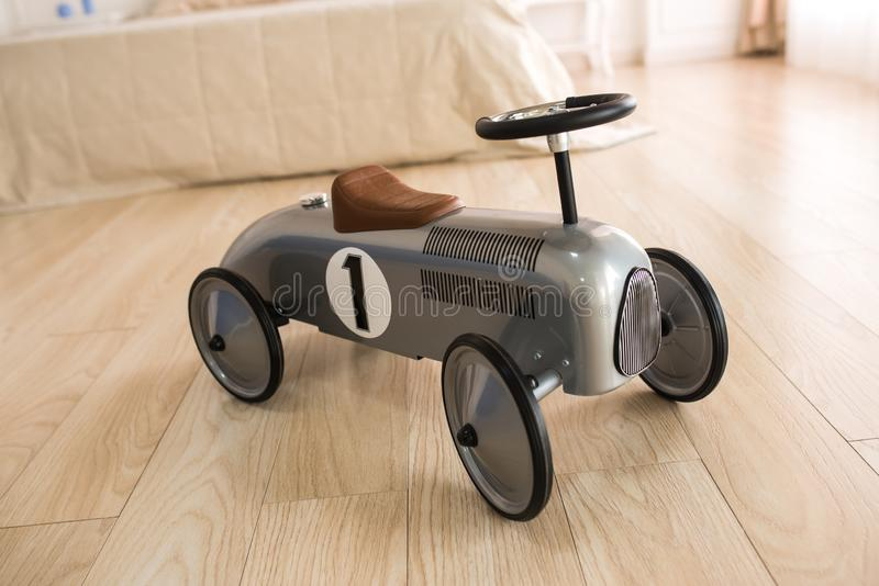 Retro car for children on a wooden floor. New silver retro car for children on a wooden floor. Element of decor stock photography