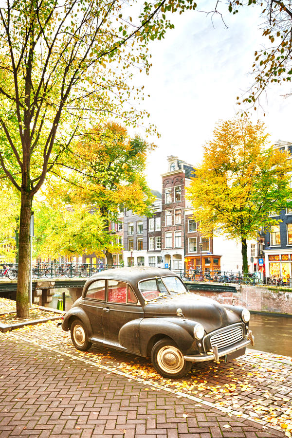 A retro car parked near a water canal. An autumn scene in Amsterdam, the Netherlands - a retro car is parked near a water canal stock photo