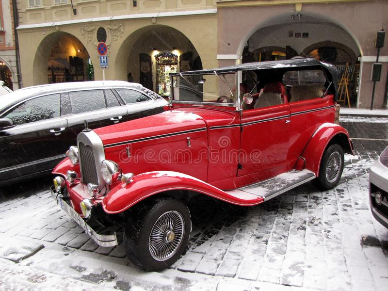 A retro car of red color on the snow-covered streets of Prague. Tourist place in the center of Europe. Medieval capital in the win royalty free stock images
