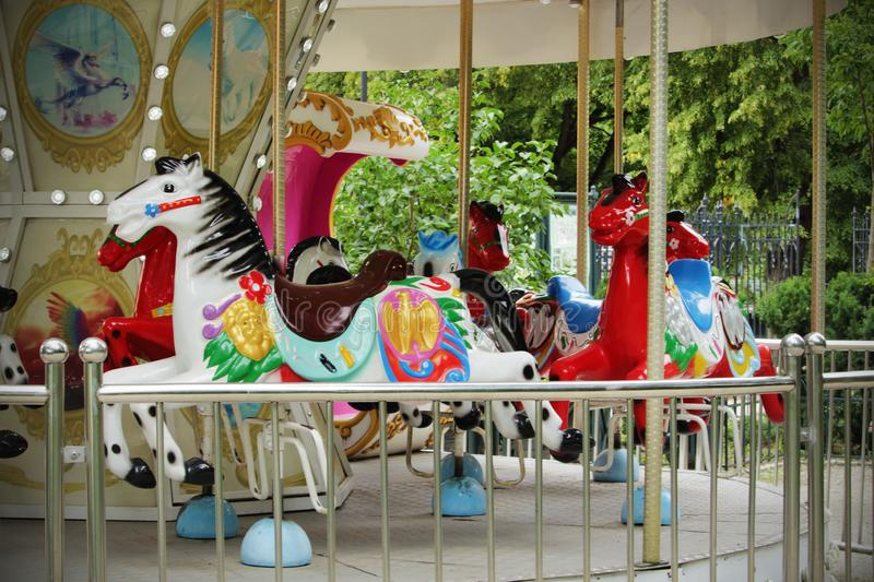 Retro carousel with colorful horses going round empty royalty free stock images