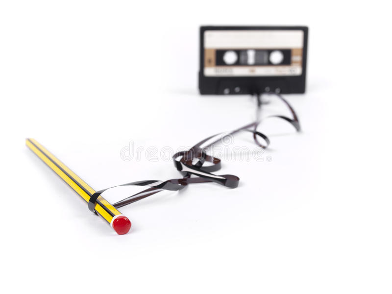 Retro cassette with loose tape and a pencil. To rewind over a white background (focus on the pencil stock images