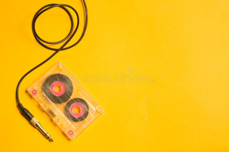 Retro cassette tape and audio jack on the yellow background. copy space stock photos