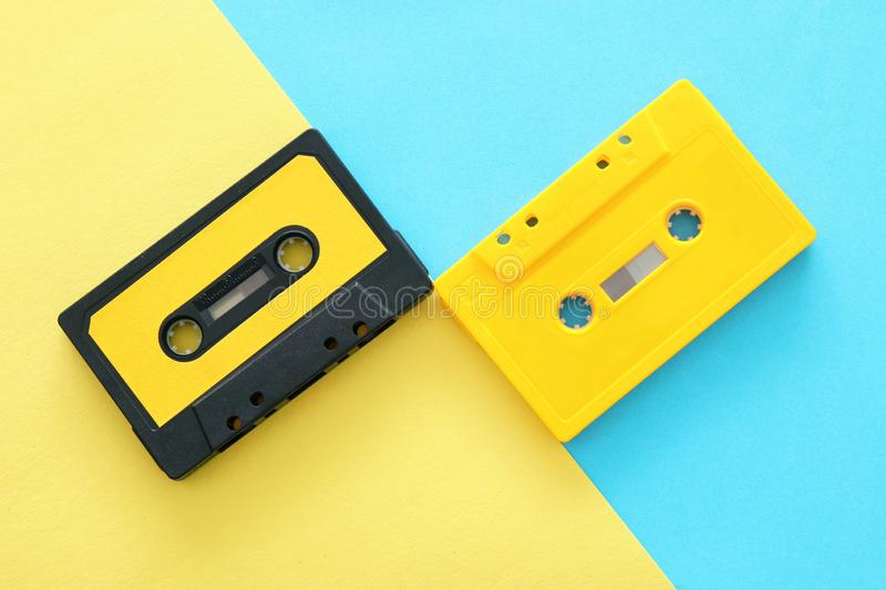Retro cassette tape over yellow and blue double colorful background. top view. copy space. royalty free stock photography