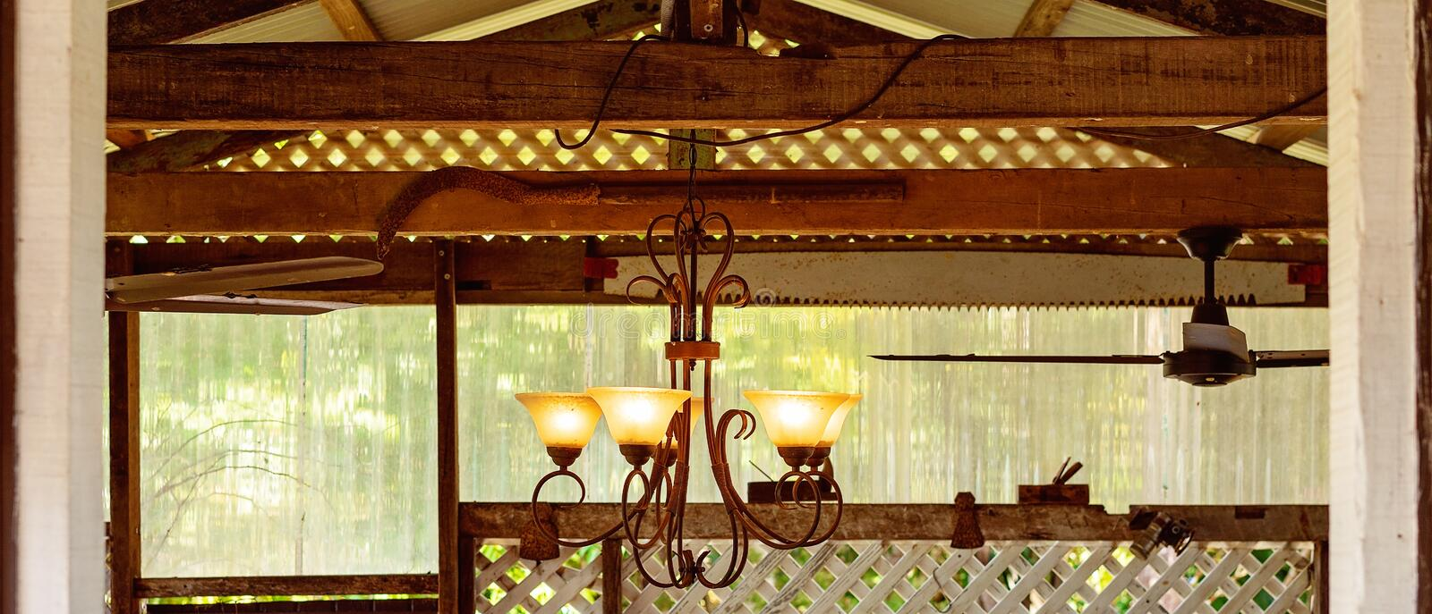 A Retro Chandelier Glowing Light In A Rustic Country Cafe. A rustic chandelier hanging from old wooden beams amongst farming objects in a country cafe royalty free stock photos