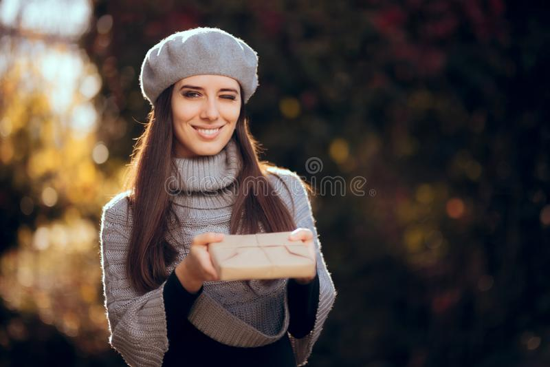 Retro Chic Girl with Beret Holding a Paper Wrapped Package. Autumn woman receiving a package by traditional mail stock images