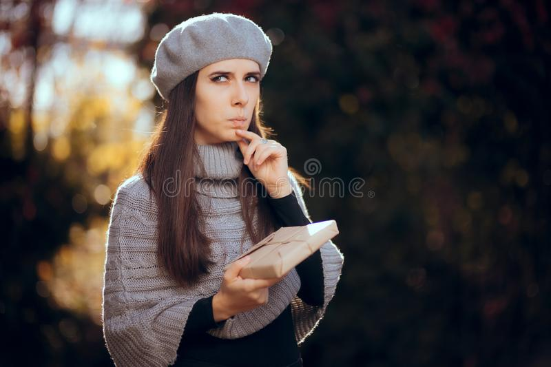 Retro Chic Girl with Beret Holding a Paper Wrapped Package. Autumn woman receiving a package by traditional mail stock photo