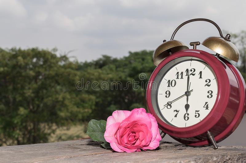 Retro clock with flowers on the wooden floor. royalty free stock photo