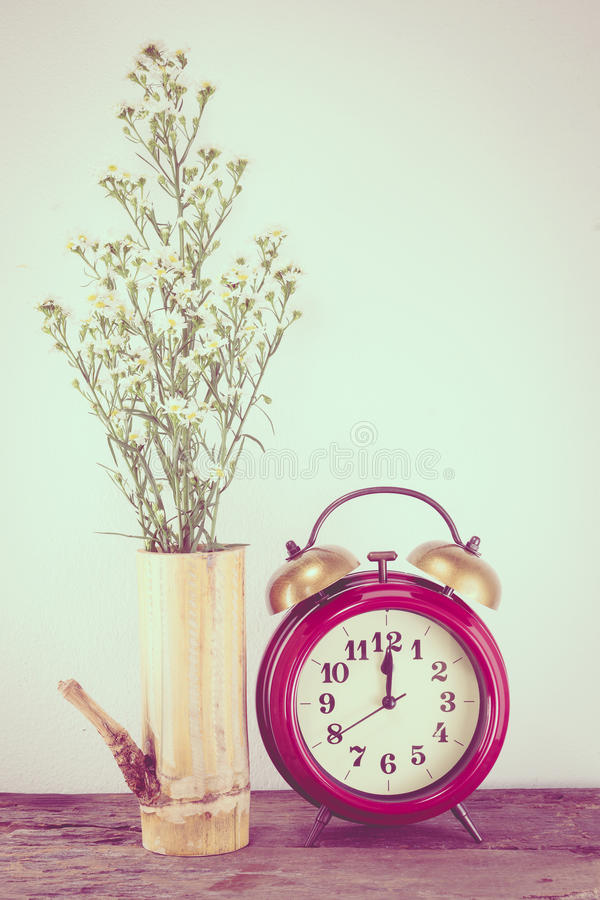 Retro clock with flowers on the wooden floor,vintage color tone. royalty free stock photos