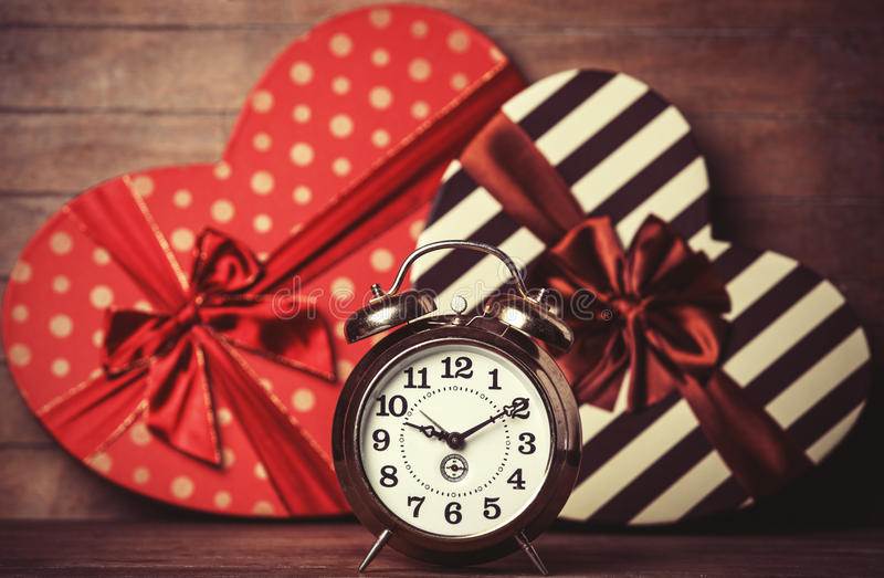 Retro clock and gift. In heart shape on the background royalty free stock photos