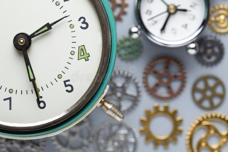 Retro clock and small parts of watch on gray background. Retro clock and small parts of watch on gray table background stock photos