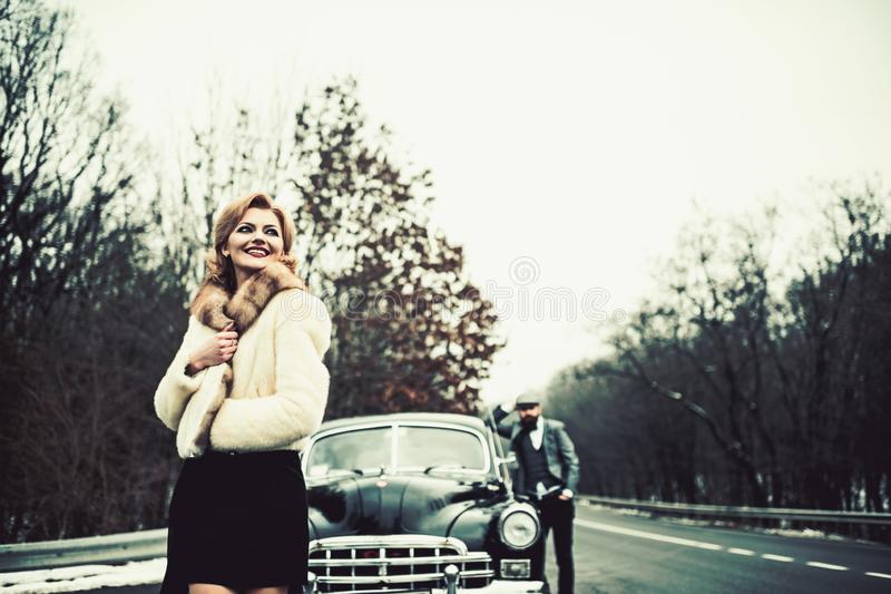 Retro collection car and auto repair by mechanic driver. Couple in love on romantic date. Escort of girl by security royalty free stock photo