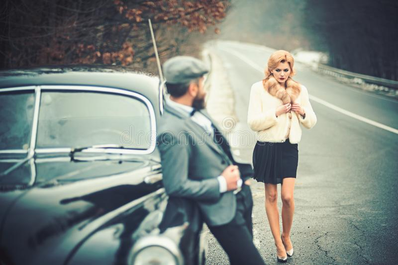Retro collection car and auto repair by mechanic driver. Escort of girl by security. Bearded man and sexy woman in fur royalty free stock images