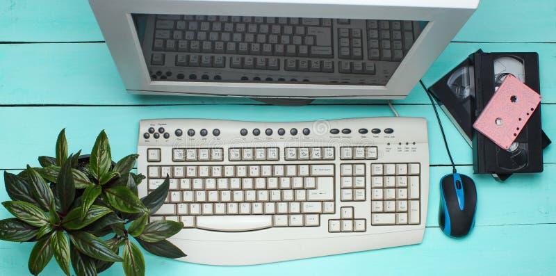 Retro computer op blauwe houten lijst Monitor, toetsenbord, PC-muis, pot met installatie, videocassette, audiocassette, hoogste m stock afbeelding