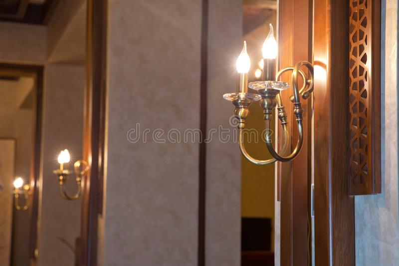 Retro copper candlestick hanging on the wall. Vintage golden candlestick with light bulbs. Gold wall candle holder on background. stock photos